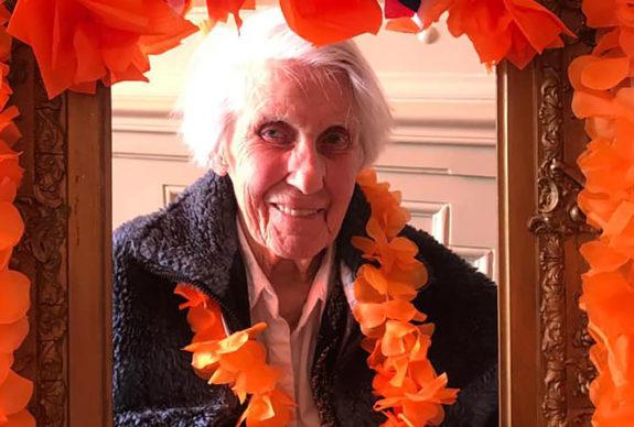 Oudere vrouw geniet in zorgvilla tijdens Koningsdag